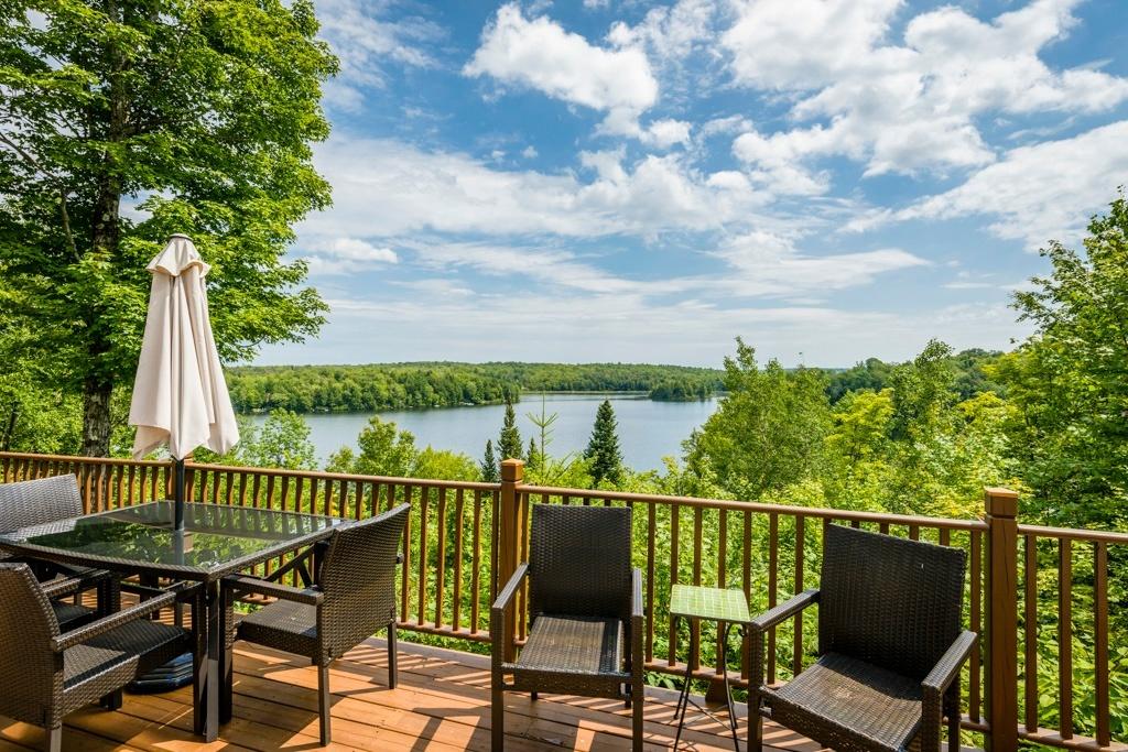 Terrasse du chalet Le Saule et SPA l'été avec vue sur le lac des Sittelles
